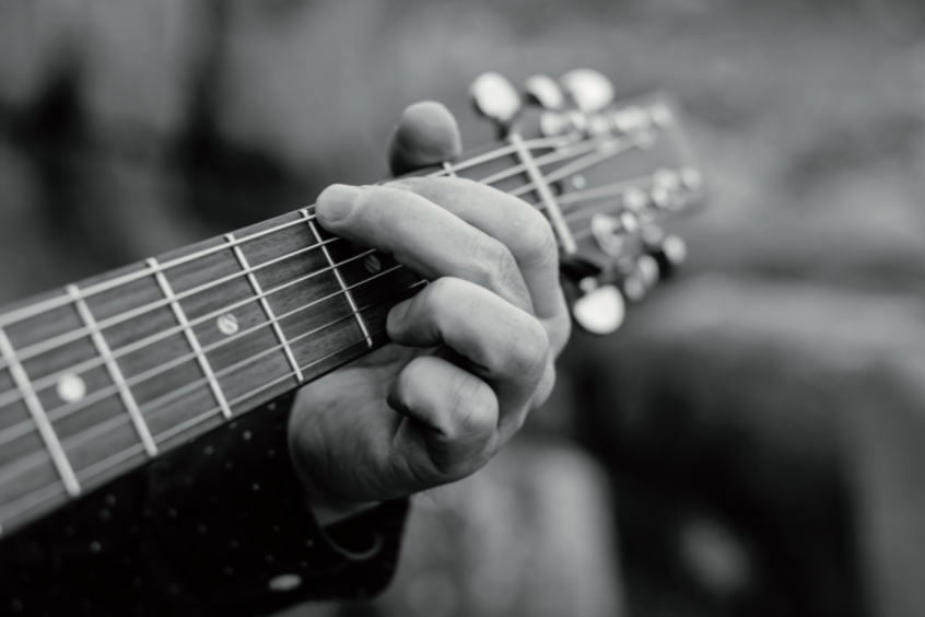 monochrome photo of playing a guiter